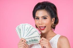 feliz hermosa mujer sosteniendo dólares
