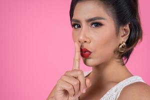 Beautiful Asian woman with red lips showing hush silence sign photo