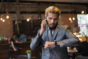Businessman talking on phone looking at hand watch photo