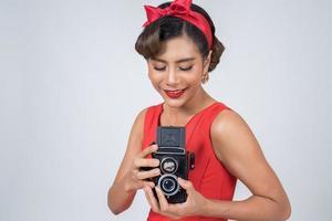 Fotógrafo de mujer de moda feliz sosteniendo una cámara retro vintage foto