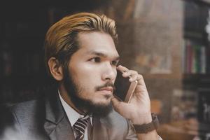 Joven empresario guapo hablando de negocios con su teléfono mientras está sentado en el bar cafetería foto