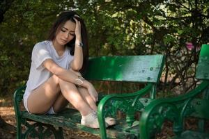 Triste mujer solitaria sentada en un banco solo en el parque foto