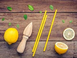 Limón fresco, exprimidor y pajitas sobre un fondo de madera foto