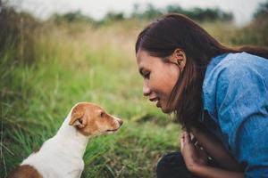 Feliz chica hipster alegre jugando con su perro en el parque durante la puesta de sol
