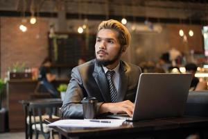 Young businessman holding cup of coffee while working on laptop computer in coffee shop photo