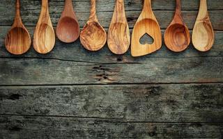 Wooden cooking utensils on shabby wooden background photo