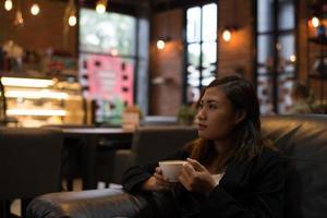 mujer joven, relajante, tomar café, en, cafe foto