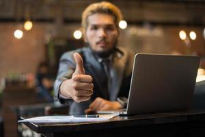 El empresario da Thumbs up mientras trabaja con un ordenador portátil en la cafetería. foto
