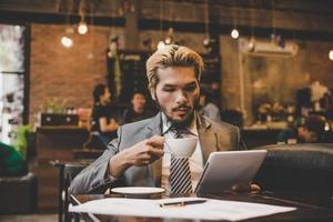 Businessman reading the newspaper and having coffee at cafe photo