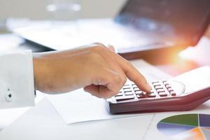 persona escribiendo en una calculadora foto