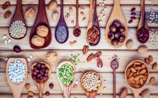 Legumes and nuts on wooden spoons photo