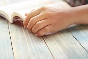 mano de una persona leyendo un libro foto