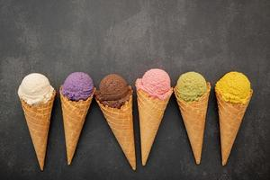 Colorful ice cream in cones on concrete