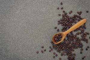 Granos de café tostado oscuro sobre fondo de piedra