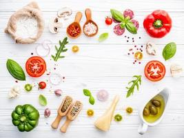 Fresh pizza ingredients on a white wooden background