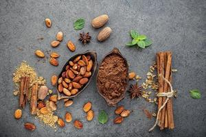 Cocoa powder and cacao beans on a stone background