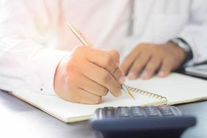 persona de negocios escribiendo en un cuaderno
