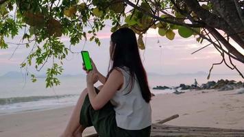 Mujer asiática haciendo una videollamada con pantalla verde