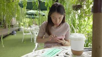 asiatische Frau mit einem Smartphone im Café