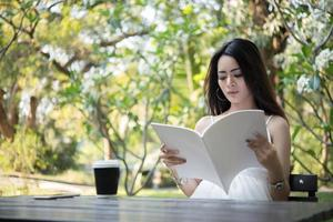 Young beautiful woman sitting and reading a book in the park