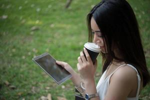 Young beautiful woman holding disposable coffee cup and smartphone outdoors