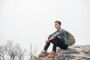 Young hipster hiker with backpack sitting on top of the mountain photo