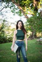 Hermosa joven sosteniendo una computadora portátil mientras se va a relajarse en el parque foto