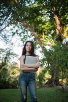 Hermosa joven sosteniendo una computadora portátil mientras va a relajarse en un parque foto
