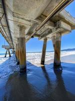 Underneath a long concrete pier on the ocean photo