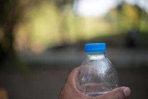 Botella de agua con fondo de naturaleza borrosa y espacio de copia foto