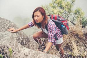 Young Asian woman hiker climbing rock on mountain peak