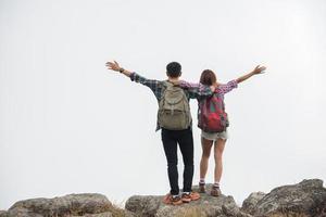 excursionistas con mochilas de pie en la cima de una montaña y disfrutando de la vista de la naturaleza