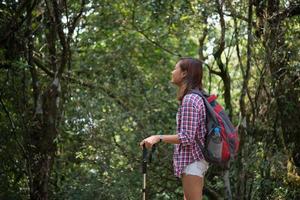 Joven excursionista mujer hipster tomando un descanso mientras camina