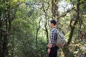 Joven excursionista hombre inconformista tomando un descanso mientras camina