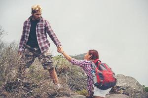 Young hipster man helping woman climb mountain