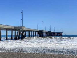 A long concrete pier on the ocean photo