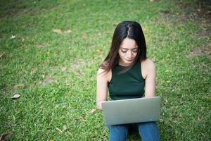 Hermosa mujer joven sentada sobre la hierba verde y usando la computadora portátil en el parque foto