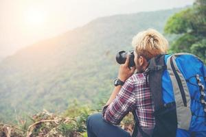 Rear of young traveller man with backpack standing on mountain and taking a photo