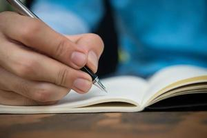 Close-up of a man writing in a notebook