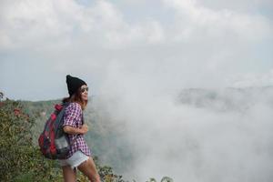 Caminante con mochila de pie en la cima de una montaña y disfrutando de la vista de la naturaleza