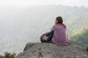 Young hiker with backpack sits on the edge of the cliff photo