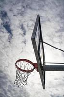 Outdoor basketball rim on a cloudy day photo