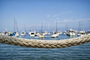 Cuerda náutica con veleros en el fondo foto