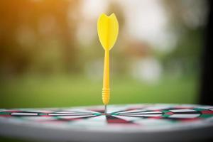 Yellow dart arrow in the center of dartboard photo