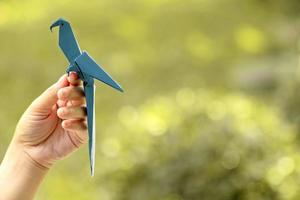 Hand holding blue origami bird with blurred nature background photo