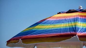 Sombrilla de playa de colores del arco iris en un día soleado