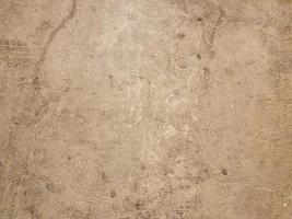 Beige plaster wall with brown paint marks