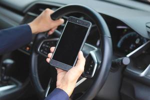 Manos sosteniendo el teléfono celular y el volante en el interior de un automóvil