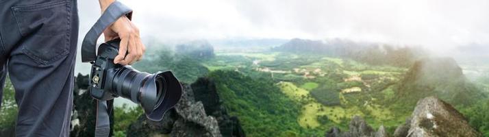 Mano sujetando una cámara digital con vistas al panorama aéreo del paisaje verde foto