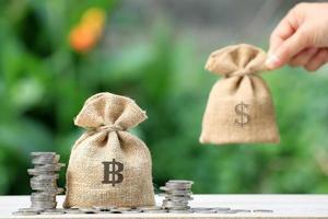 Mano con sacos de dinero de arpillera junto a pilas de monedas foto